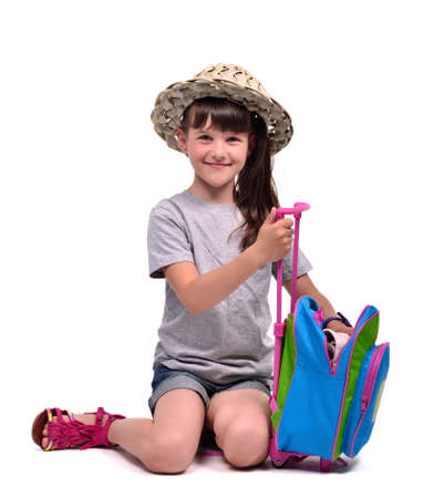 Little girl packing her staff to go to vacation isolated on white background