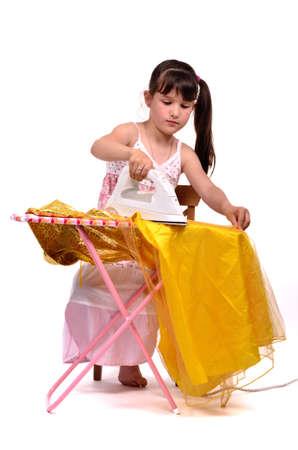 Dangerous housework - little, brunette hair girl ironing her dress photo