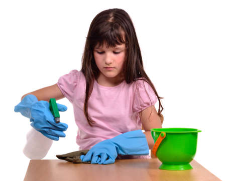 laborious: Little girl creaning her desk with cleaning supplies isolated on white background Stock Photo