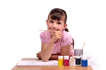 Little girl painting a picture with colorful paints isolated on white background photo