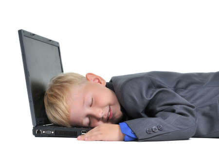 Boy sleeping on laptop tired of work, isolated on white photo