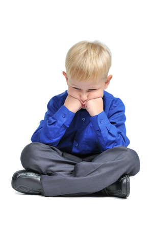 Sad boy with suit sitting in lotus pose isolated photo