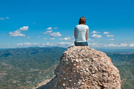 blue sky thinking: Young girl sitting on an edge of a cliff, Montserrat mountain, Spain Editorial