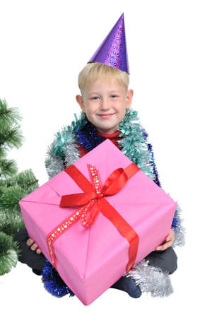 Smiling little boy with Christmas present near new year tree photo