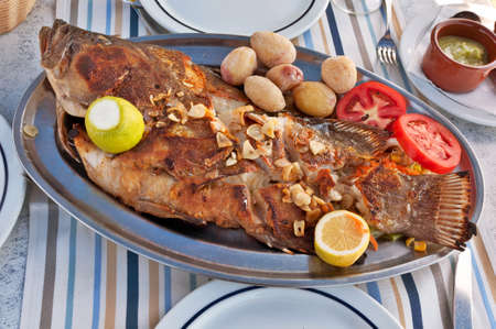 Roasted sea fish on plate with tomatoes, potatoes, lemon and spices photo