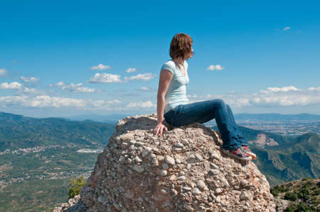Young girl sitting on an edge of a cliff, Spain photo