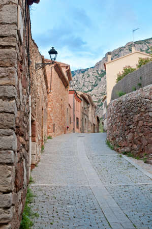 Empty street in in old village near Montserrat mountain, Collbato, Spain photo