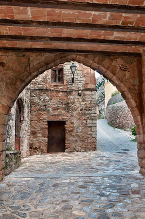 Narrow medieval street with an arch, Collbato, Spain. Stock Photo - 12080421