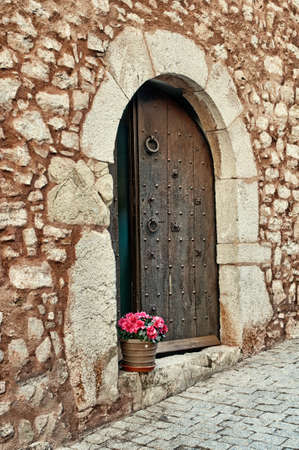Pot of red flowers on a doorstep of a medieval wal in Spain, Collbato, Spain photo