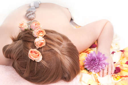 sensual massage: Beautiful woman with spa stones on her back.