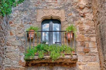 Small balcony with flowers on a stone wall in Peratallada, Spain. photo