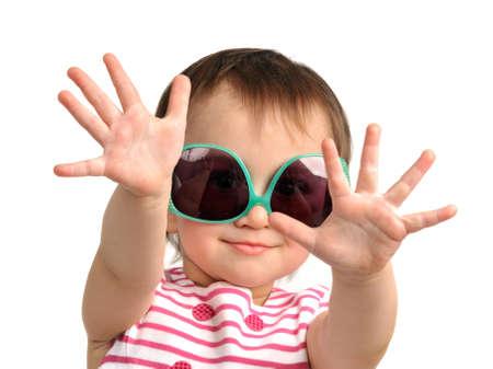 Petite fille mignonne portant lunettes de soleil isolé Banque d'images