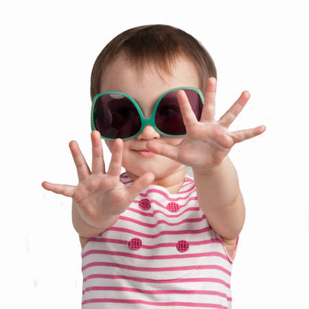 Cheerful little girl wearing glamorous glasses isolated photo