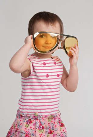 Little girl wearing huge glasses, studio shot photo