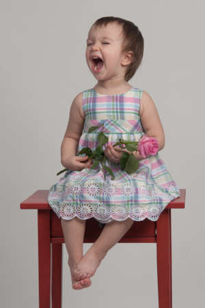 Crying baby girl holding flower photo
