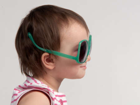 misconception: Cute child wearing glasses in a wrong way, side view Stock Photo