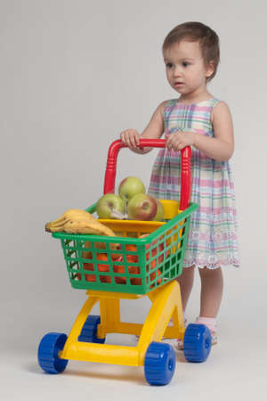 Shopping concept - child with shopping cart full with groceries photo