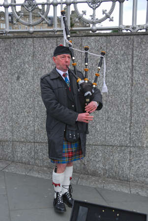 Scottish Bagpiper in uniform, in plaid and kilt with the Bagpipe, Princess Street, Edinburg, Scotland