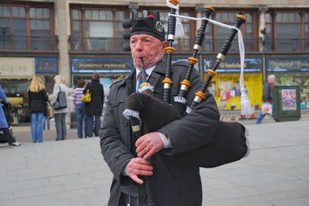 gaita: Gaitero escocés en el uniforme, en la falda a cuadros y con la gaita, Princess Street, Edimburgo, Escocia