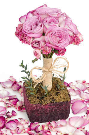Pink roses bouquet in handmade basket surrounded with petals Stock Photo - 12615785