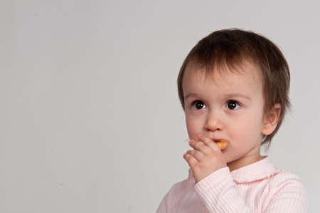 Portrait of litlle girl eating snacks photo