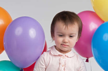 Sad baby girl with balloons photo