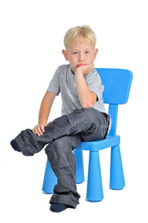 baby chair: Sad boy sitting on a chair, isolated on white background