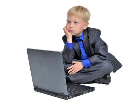 Thoughtful boy with computer, isolated on white background  photo