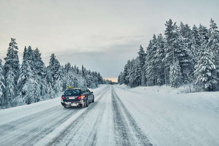 lapland: Taxi overtaking on a slippery winter road in Lapland Stock Photo