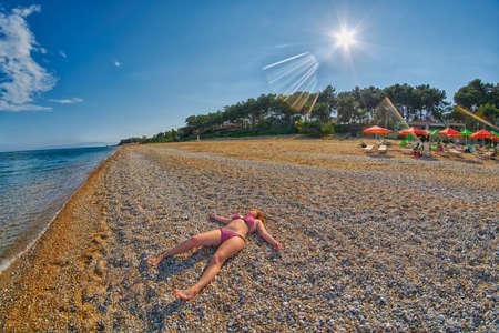skala: Young Girl Relaxing on a Skala Beach in Kefalonia, Greece Stock Photo
