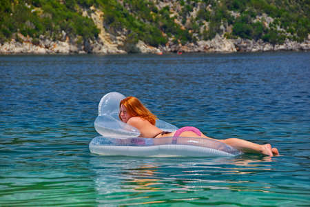 matress: Young Woman in inflatable Matress relaxing in the Sea