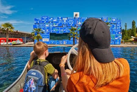 union familiar: Luzern, Suiza - el 10 de agosto de 2016: Los niños disfrutan de paseo del barco en el Museo de Transporte de Suiza con las señales de tráfico como telón de fondo