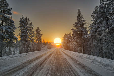 rovaniemi: Bright Colorful Winter Polar Night Sunset over road in Lapland, Finland Stock Photo