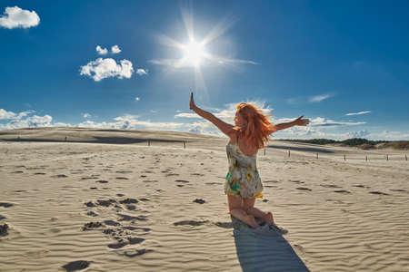 Happy Redheaded woman waving hands under sunshine among Leba dunes Desert of Polish Baltic shore