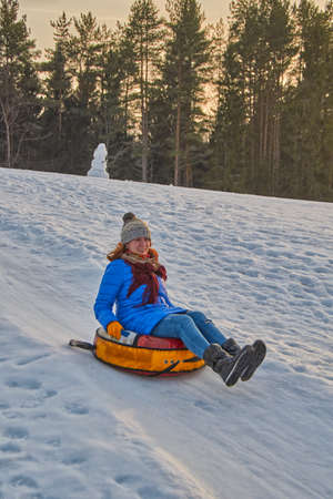 Happy Young Woman on a fast Sleigh Ride down the icy slope Stock Photo