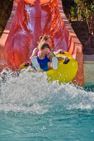 summer holidays: Happy mother and her daughter enjoy water slides in Aqua Park