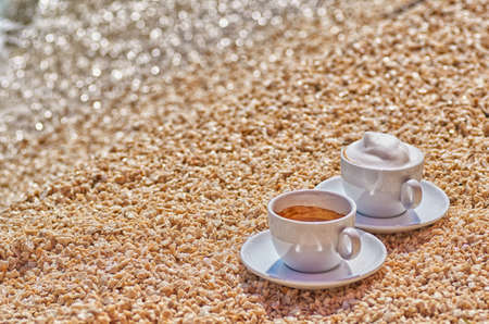 Two coffee cups, Espresso and Cappucino at the Sea Shore on the Beach Stock Photo