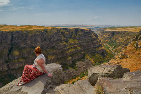 Young woman sitting on the edge of Kasagh river gorge near Saghmosavank monastery