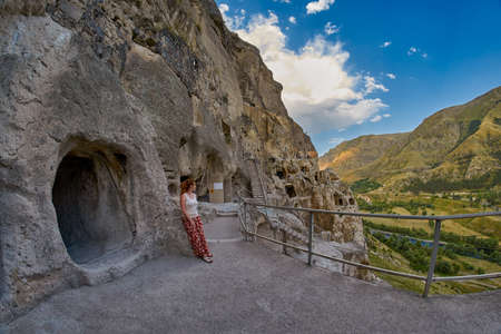 Young woman in famous Vardzia Cave Town Monastery Landmark of Georgia