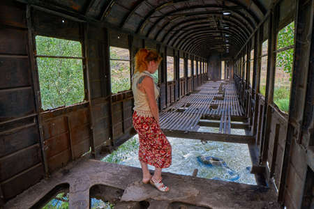 Young woman inside of Strange bridge made from old abandoned train car in Georgia Imagens