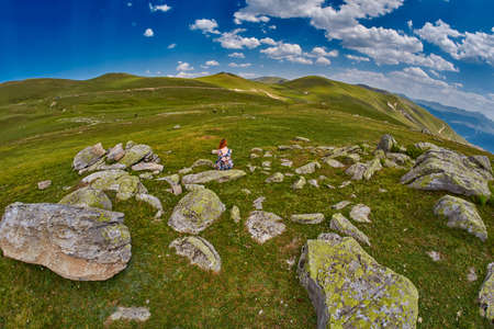 Young woman getting inspiration in high mountain valley rocky plains