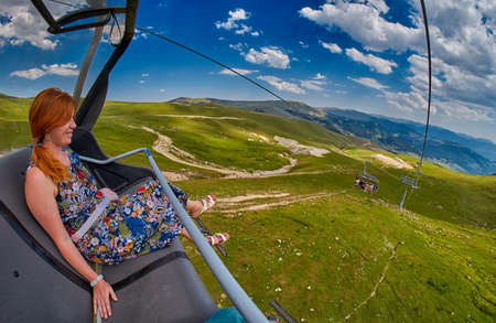 Young redheaded woman enjoying a ride on an open-air ropeway in scenic mountains  Imagens