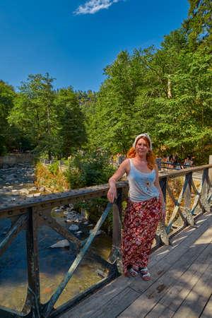 BORJOMI, GEORGIA - 07 August 2017: Woman on a river bridge in  Borjomi town central park forest walkway