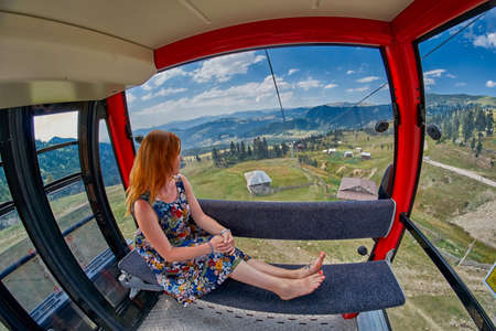 Young woman in cable car cabin in Georgian mountains
