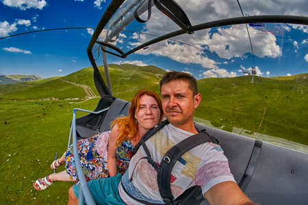 ADJARA, GEORGIA - 08 AUGUST 2017: Happy tourists riding open air cable car over mountain landscapes in Georgian remote countryside