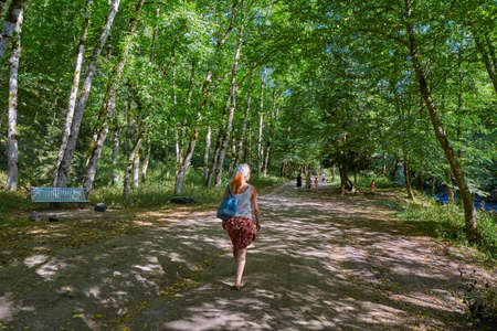 Woman leaning against tree in  Borjomi town central park forest walkway