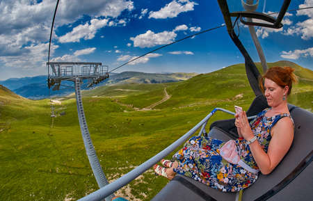 Young redheaded woman chatting with friends in social networks while riding ropeway high in mountains