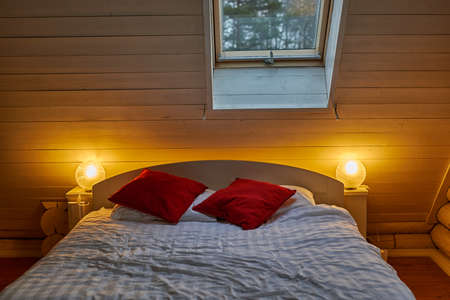 Cozy double bed in a bedroom in country house or hotel in morning light
