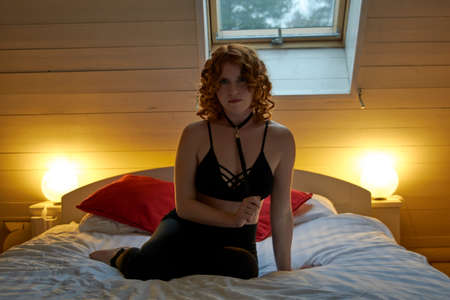 Young redheaded woman with sexy leather neck choker in romantic country bedroom settings