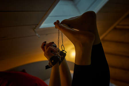 Artistic image of female hands and feet with handcuffs in dimmed light room 写真素材